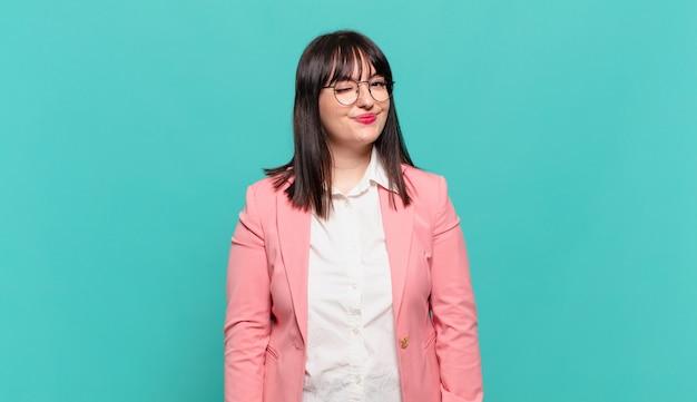 Giovane donna d'affari che sembra felice e amichevole, sorride e ti fa l'occhiolino con un atteggiamento positivo