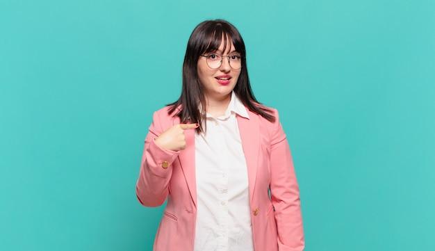 Giovane donna d'affari che sembra felice, orgogliosa e sorpresa, indicando allegramente se stessa, sentendosi sicura e nobile