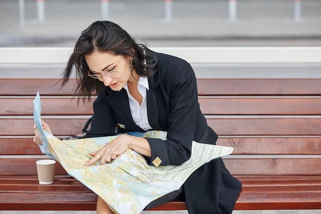 Una giovane donna d'affari alla ricerca di qualcosa sulla mappa seduto sulla panchina