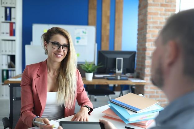 La giovane donna di affari in ufficio sta intervistando l'uomo