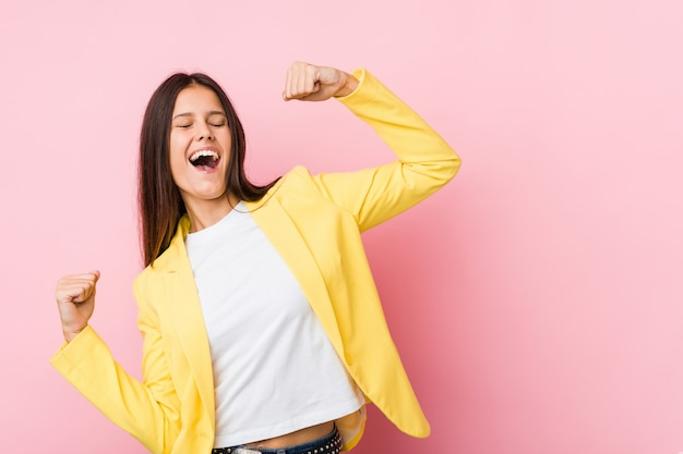Giovane donna di affari che alza pugno dopo una vittoria, concetto del vincitore.