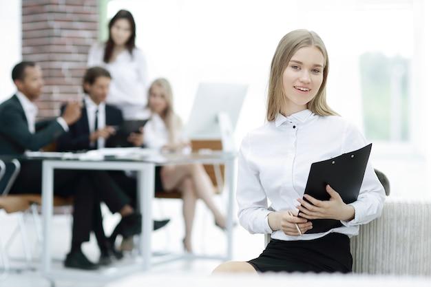 Documento di lettura della giovane donna di affari nel suo ufficio
