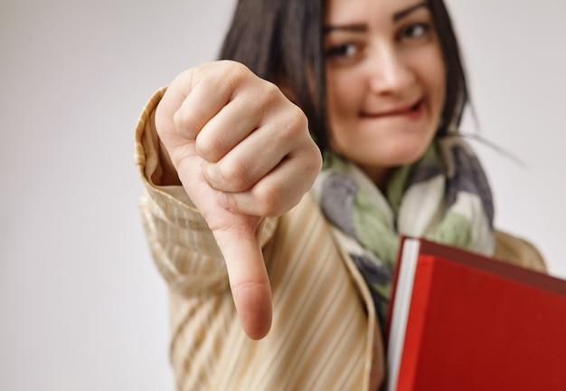 Giovane donna di affari che mostra il suo dito verso il basso