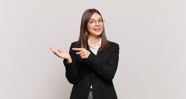Giovane donna d'affari che sorride allegramente e punta a copiare lo spazio sul palmo sul lato, mostrando o pubblicizzando un oggetto