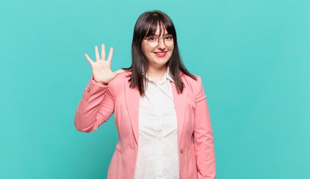 Giovane donna d'affari sorridente e dall'aspetto amichevole, mostrando il numero cinque o il quinto con la mano in avanti, conto alla rovescia