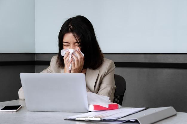 Giovane donna d'affari starnuti mentre si lavora in sala riunioni. concetto di inflessione lavorativa e stagionale