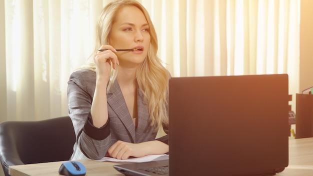 La giovane donna di affari in vestito lavora al computer in ufficio.