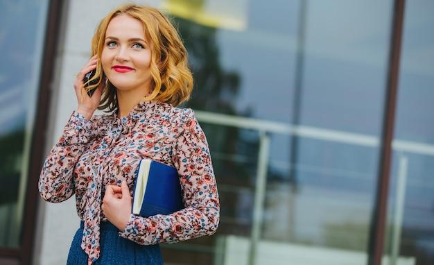 Giovane donna d'affari parlando al telefono in ufficio