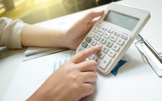 Giovane donna d'affari utilizzando calcolatrice