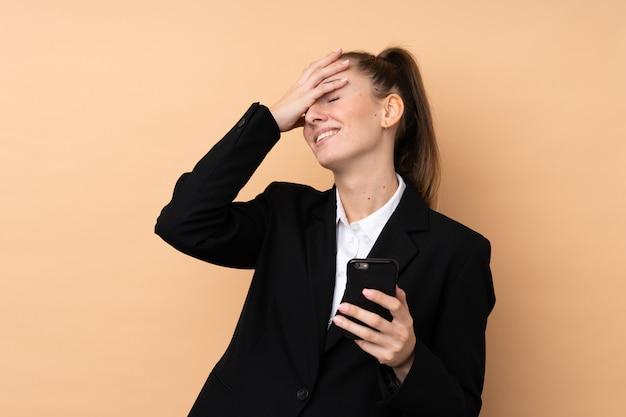 La giovane donna di affari che per mezzo del telefono cellulare sopra la parete isolata ha realizzato qualcosa e intende la soluzione