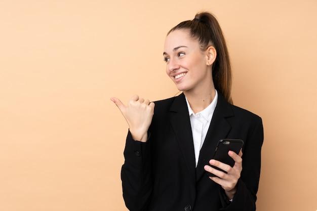 Giovane donna d'affari utilizzando il telefono cellulare sul muro isolato che punta verso il lato per presentare un prodotto