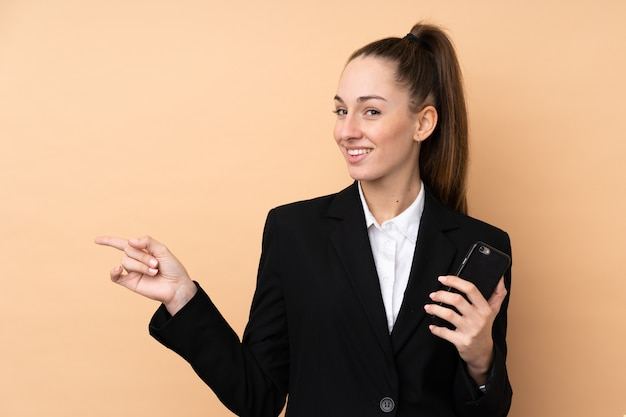 Giovane donna d'affari utilizzando il telefono cellulare su muro isolato sorpreso e puntando il dito verso il lato