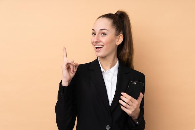 Giovane donna di affari che per mezzo del telefono cellulare sopra il wallpoint isolato su una grande idea