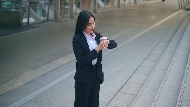 Una giovane donna d'affari che indossa un abito nero si affretta durante l'ora di punta mattutina, tenendo in mano una tazza di caffè a piedi in città, concetto di stile di vita aziendale.