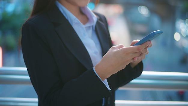 Una giovane donna d'affari che indossa un abito nero sta usando smart phone, in città, business lifestyle concept.