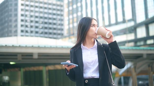 Una giovane donna d'affari che indossa un abito nero sta usando smart phone