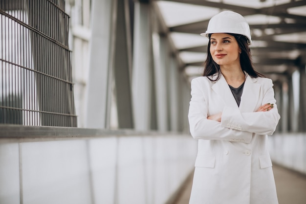 Giovane donna d'affari che indossa elmetto durante la costruzione di oggetti