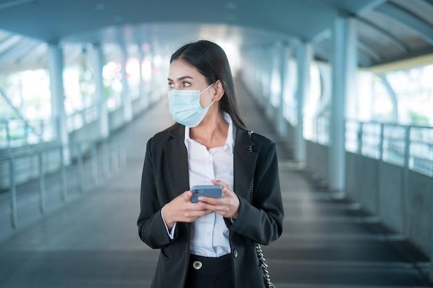 La giovane donna di affari con la maschera facciale è in piedi sulla piattaforma della metropolitana utilizzando smart