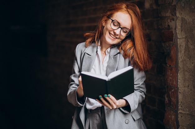 Giovane donna d'affari con i capelli rossi che legge un libro
