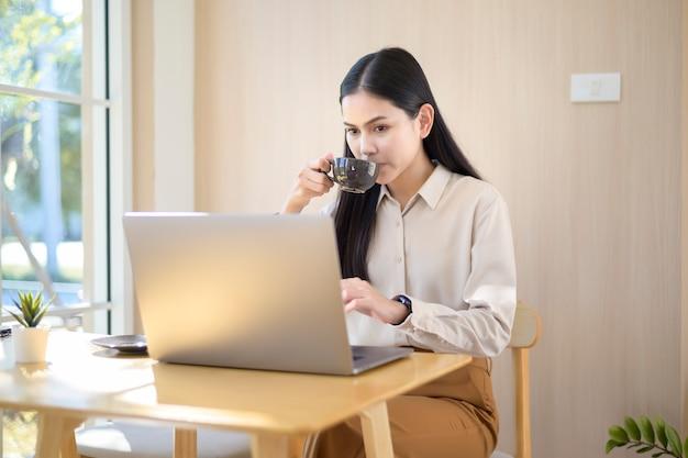 Una giovane donna d'affari che lavora con il suo computer portatile in una caffetteria
