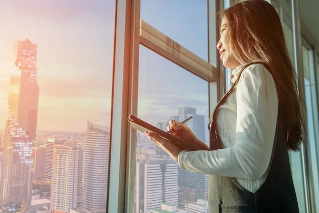 Una giovane donna di affari che scrive un computer tablet in ufficio con la costruzione della città sullo sfondo.