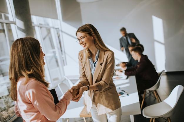 Giovani donne d'affari dando amichevole stretta di mano in ufficio