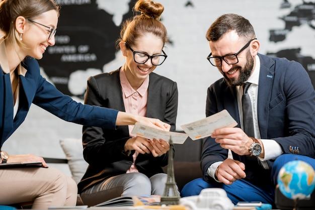 Giovane coppia di affari che sceglie un viaggio con un agente seduto nell'ufficio dell'agenzia di viaggi con la mappa del mondo sullo sfondo