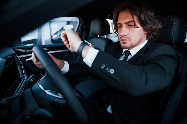 Giovane uomo d'affari in abito nero e cravatta alla guida di un'automobile moderna.