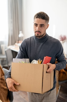 Giovane uomo d'affari che trasporta una scatola con forniture mentre cambia posto di lavoro