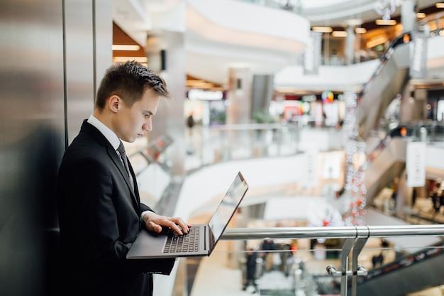 Giovane imprenditore controlla business su laptop, indoor, vista profilo, vestito in abito nero nel centro commerciale,