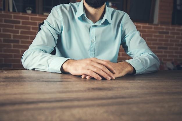 Il giovane imprenditore attraversa le mani sulla scrivania
