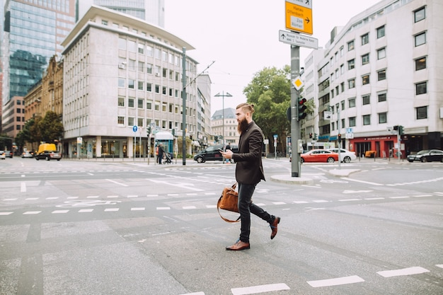 Il giovane uomo d'affari attraversa la strada nella bellissima città