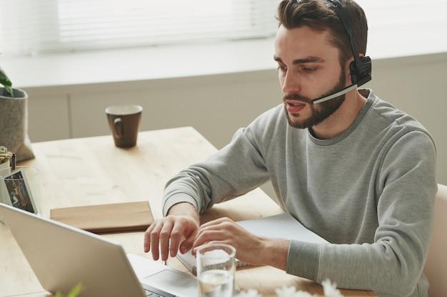 Giovane imprenditore o rappresentante del servizio clienti con auricolare seduti a tavola davanti al computer portatile e consultare i clienti online a casa