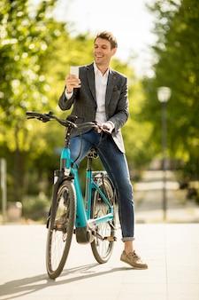 Il giovane uomo d'affari sull'ebike fa la fotografia del selfie con il telefono cellulare