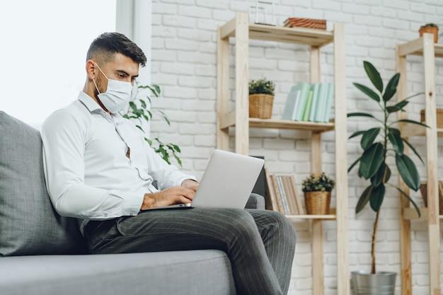 Giovane imprenditore in maschera per il viso seduto sul divano e utilizzando laptop a casa
