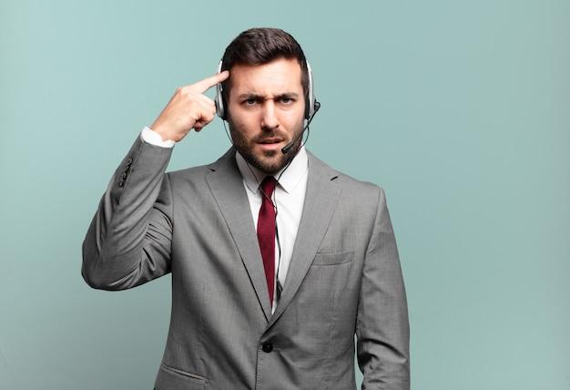 Giovane imprenditore sentirsi confuso e perplesso, dimostrando che sei pazzo, pazzo o fuori di testa per il concetto di telemarketing