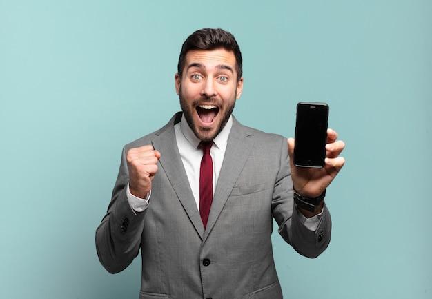 Giovane imprenditore che si sente scioccato, eccitato e felice, ridendo e celebrando il successo, dicendo wow! e mostrando lo schermo del suo telefono