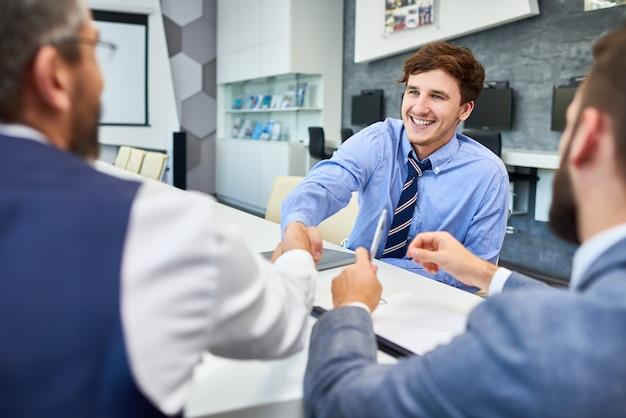 Giovane uomo d'affari nel saluto partner nella riunione