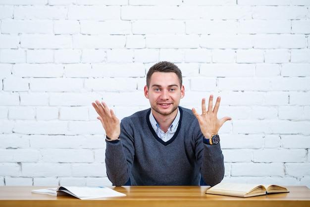 Un giovane uomo d'affari si siede a un tavolo con un libro