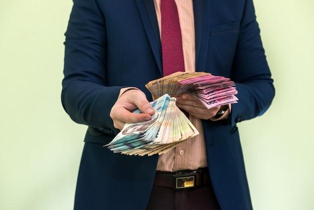 Giovane uomo d'affari che tiene un'enorme quantità di denaro. nuove banconote uah dell'ucraina 1000 e 500 nelle mani di un uomo d'affari. profitto.