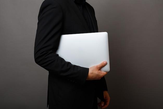 Il giovane uomo d'affari tiene un computer portatile su uno sfondo grigio