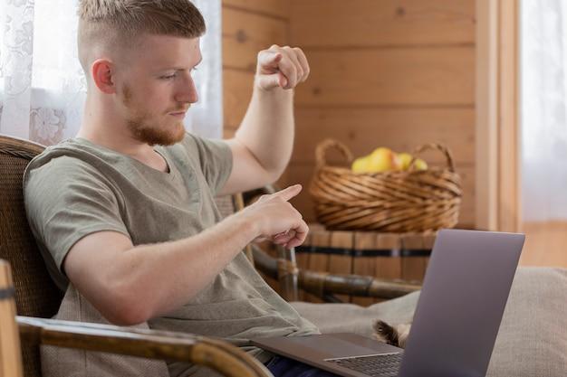 Il giovane uomo d'affari sta partecipando a una riunione con i colleghi su internet utilizzando un laptop in remoto da casa