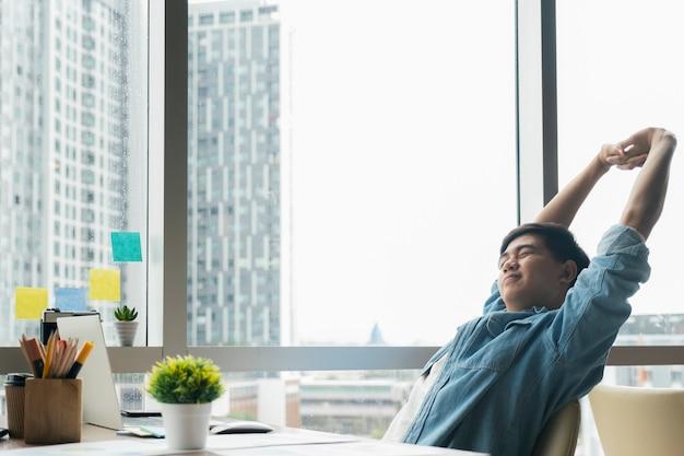 Il giovane uomo d'affari sta rilassandosi in ufficio e sta allungando il suo corpo