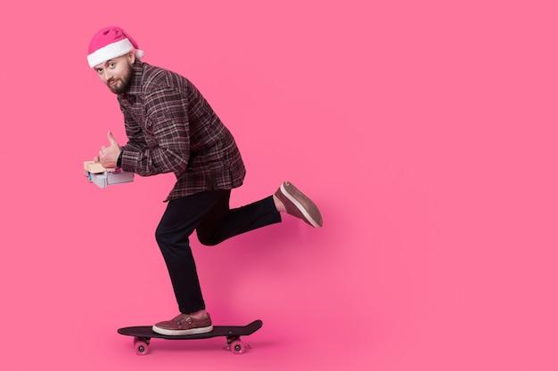 Il giovane uomo d'affari sta cavalcando sullo skateboard che indossa un cappello da babbo natale e che tiene i regali sul muro rosa con spazio libero
