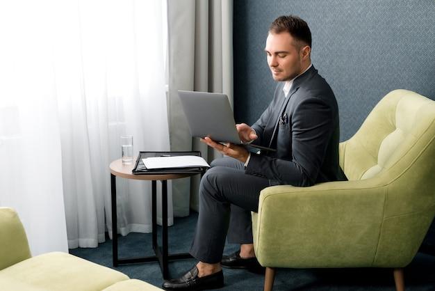 Il giovane uomo d'affari sta usando il portatile mentre era seduto nella camera d'albergo con la valigia.