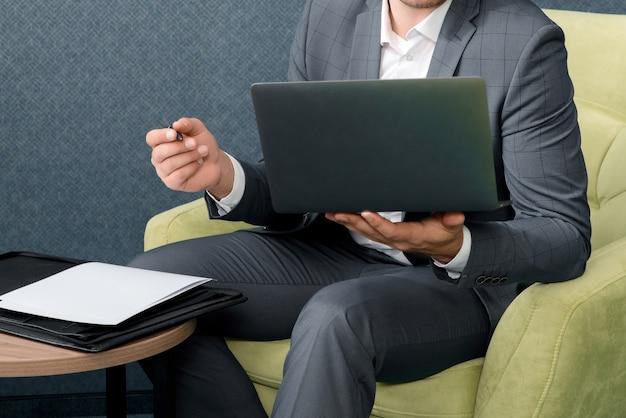 Il giovane uomo d'affari sta usando il computer portatile e sta lavorando con i documenti mentre si siede nella camera d'albergo con la valigia.