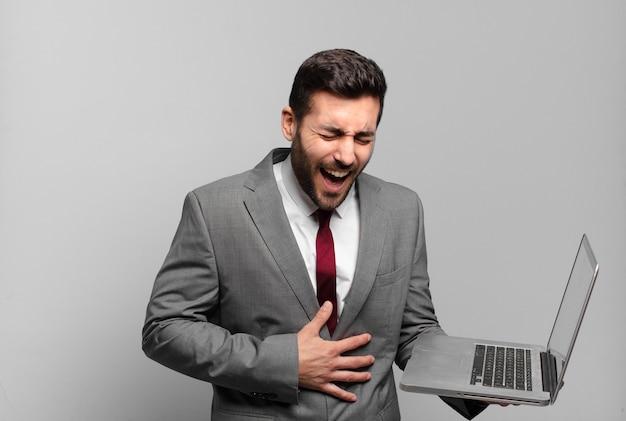 Giovane uomo d'affari che ride ad alta voce a uno scherzo esilarante, sentendosi felice e allegro, divertendosi e tenendo in mano un laptop