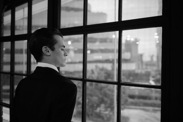 Giovane imprenditore guardando fuori dalla finestra e pensando