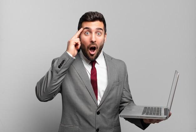 Giovane uomo d'affari che sembra sorpreso, a bocca aperta, scioccato, realizzando un nuovo pensiero, idea o concetto e tenendo in mano un laptop