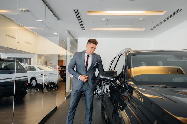 Un giovane uomo d'affari guarda una nuova auto in una concessionaria di automobili